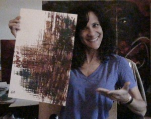 Cheryl Green holds an earth-toned abstract painting on white paper and smiles for the camera.