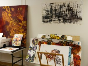 Abstract paintings on displayon the wall, resting on a table, or stacked. Images show rich, dark colors, vibrant lines and spheres, and splashes.