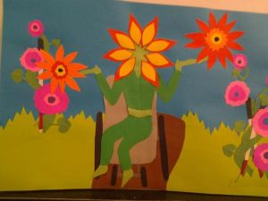 A green human figure sits in a brown chair. Its head is a large, vibrant flower, and its hands are open to the sky. All around the figure are other bright pink, yellow, orange, and red flowers. The images are all cut paper, and you can see the layers and texture of the paper.