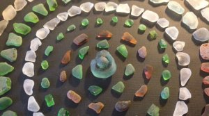 Six rings made of small beach glass pieces are visible, making up a mandala. Each ring is one color family, and the rings are pinks, greens, whites, and reds. In the center is a larger piece of beach glasses. The rings are on rich brown, textured paper.