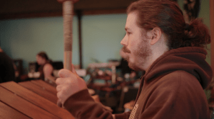 Brandon, now with beard and hair in a ponytail, plays a large marimba with thick mallets.