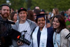 Four people smile for the camera:  Shawn and Paulius hold their recording equipment, Dani is in blue and white high school graduation cap and gown, and Athena is in a striped sweater.