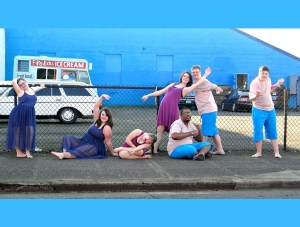 Seven teen and young adult dancers strike poses in front of a bright blue building.