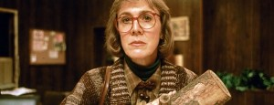 [A close up of The Log Lady, cradling her log, looks intently at the camera and listens closely.