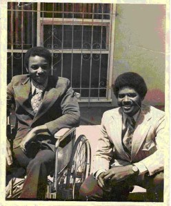 Old photo of two smiling Black men in suits: Brad Lomax in a wheelchair and Glen Lomax, crouching down.