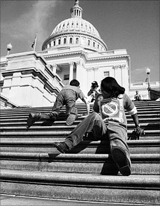 "Image of three people crawling up US Capitol building. Main person in photo is a young black woman crawling up backward. Image from ""Lives Worth Living"" movie."