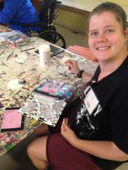 A woman smiles for the camera and shows off her colorful collage project, a handmade journal.