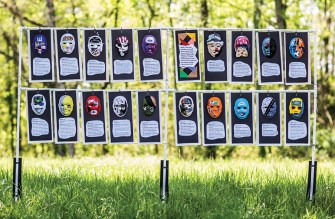 20 multi-colored, hand-decorated masks hang outside with a short story beneath each one.