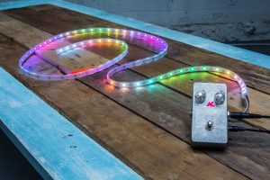 AudioLux one: a small silver box connected to a flexible strip covered in small, colored lights.