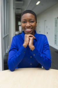 Talila Lewis, a Black person with short hair wearing a cobalt blue button-down shirt, clasping hands together, and smiling for the camera.