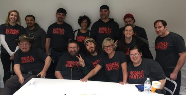 "13 people smiling for the camera. 12 are wearing matching shirts with ""Normal Is A Fantasy"" in red letters. Most people in the photo have a TBI or an ABI, and some have other disabilities too."