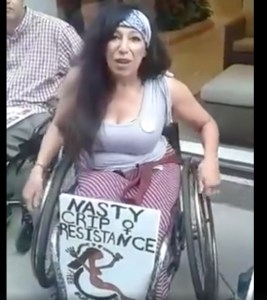 "Maria Palacios, a Latina in a tank top and skirt, sits in a manual wheelchair. Resting on her legs is a sign: ""Nasty Crip Resistance. Free our people."" There is a Venus woman power symbol and a nude Brown woman in a wheelchair, arms raised, chains around her wrists broken, adapted from the ADAPT logo."
