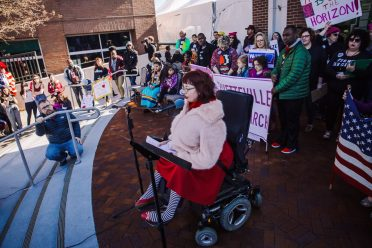 Caitlin Wood, a white woman in bright red dress, fuzzy coat, and striped stockings sits in a power wheelchair and addresses a crowd. Behind her stand and sit people of various ages, ethnicities, and genders holding Fayetteville Women's March signs.