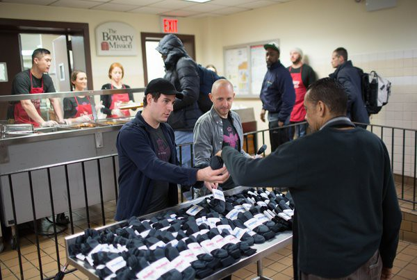 The Bombas founders Randy Goldberg, left, and David Heath passing out pairs of socks at the Bowery Mission in Manhattan. For every pair they sell, they give away another. KEVIN HAGEN FOR THE NEW YORK TIMES