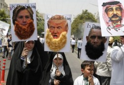 """Iranian protesters hold portraits of (from L to R) US Democrat presidential candidate Hillary Clinton, US Republican presidential candidate Donald Trump, US President Barack Obama and Bahraini King Hamad, most adorned with jihadist-style beards and a slogan reading """"is Daeishian"""" (Daesh is Arabic acronym for Islamic State), during a parade marking al-Quds (Jerusalem) Day in Tehran on July 01, 2016. Tens of thousands joined pro-Palestinian rallies in Tehran, as the annual Quds Day protests take on broader meaning for a region mired in bitter disputes and war. / AFP PHOTO / ATTA KENARE"""