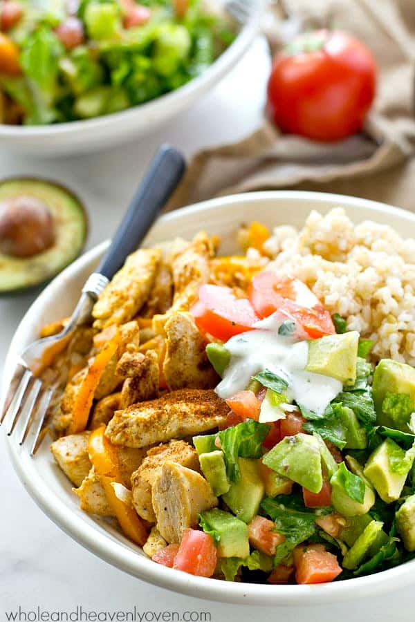 Zippy cajun-rubbed chicken, hot rice, and an amazing fresh avocado salad come together in these beautiful AND easy-to-throw together healthy rice bowls!