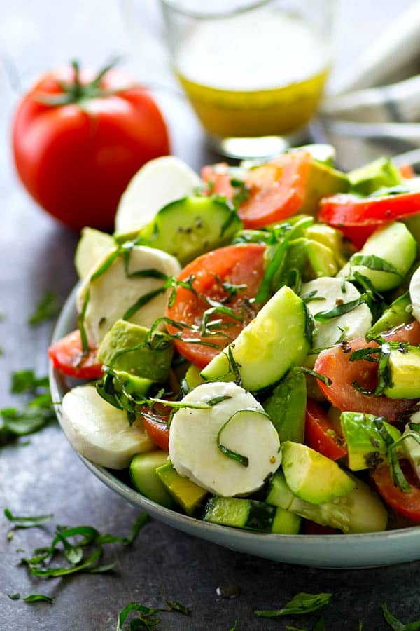 This Italian-style tomato avocado salad is loaded with tons of fresh tomatoes, avocados, cucumbers, and soft mozzarella cheese for one killer summer salad!