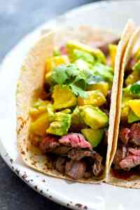 Tender flank steak is marinated in a citrus marinade and grilled until INSANELY juicy. Pile it all into these loaded steak tacos with tons of flavorful orange avocado salsa on top!