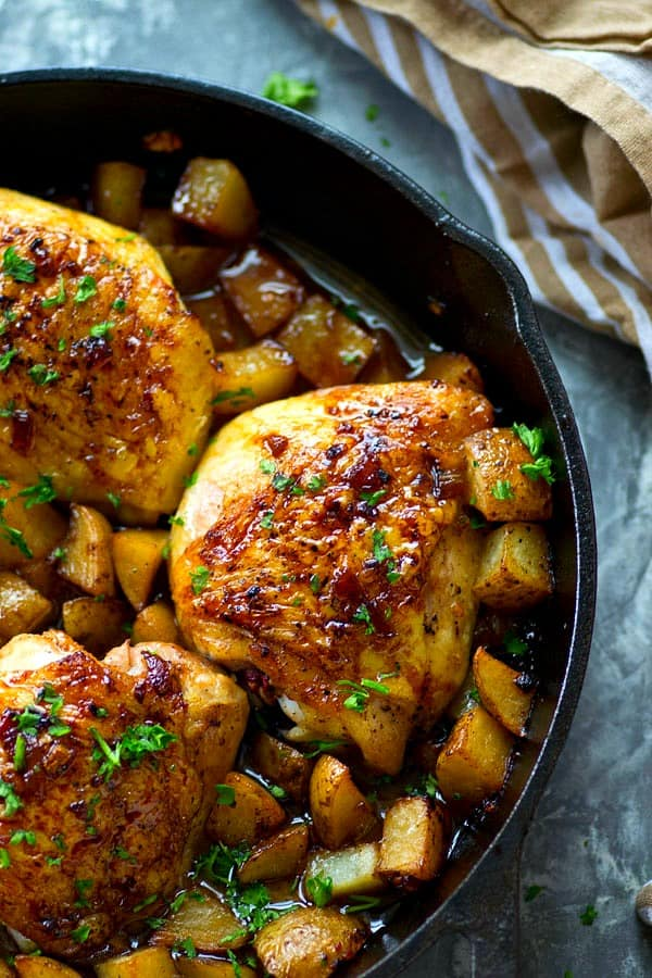 Juicy honey garlic chicken thighs and crispy roast potatoes are seared and baked in the most FLAVORFUL honey garlic sauce in this no-fuss one skillet dinner!