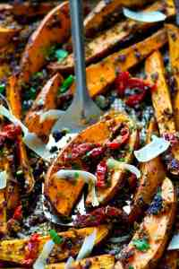 Roasted in a flavorful homemade sun-dried tomato pesto and covered in shaved Parmesan, these sweet potato wedges are SUCH an easy dinner side and you'll be eating them straight off the pan.