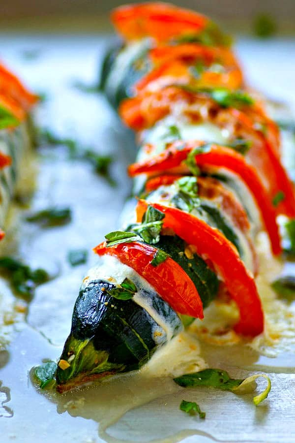 These hasselback caprese zucchini boats are stuffed with juicy tomato slices, gooey mozzarella, and tons of fresh basil for a seasonal veggie side that's LOADED with summer flavors!