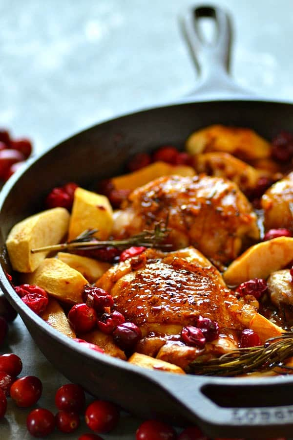 Juicy chicken thighs are roasted in tangy cranberries, soft apples, and covered in a sweet maple glaze for the EASIEST way to do chicken holiday-style!