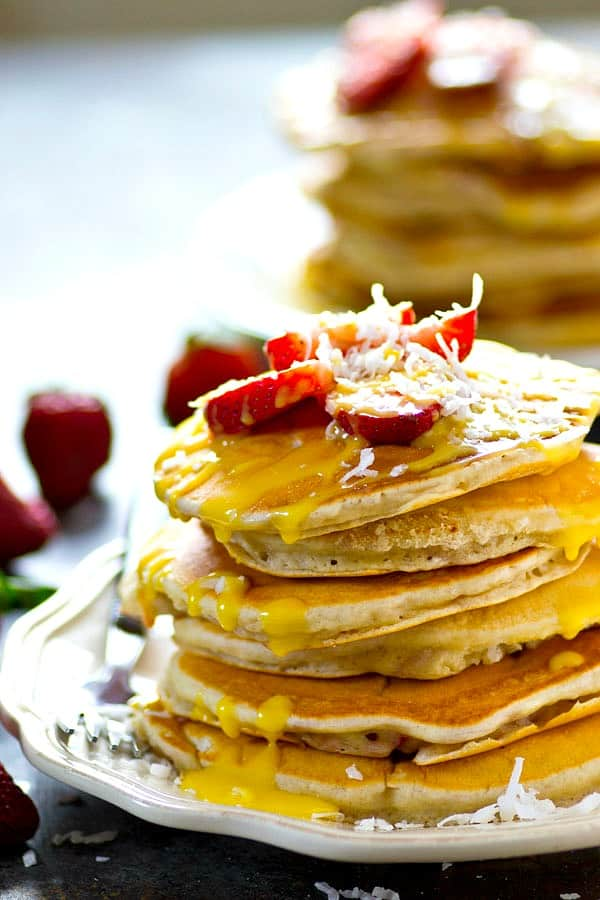 Incredibly light and fluffy, studded with juicy strawberries, and covered in a tangy homemade lemon curd, these strawberry coconut lemon curd pancakes are the ULTIMATE pancake breakfast!