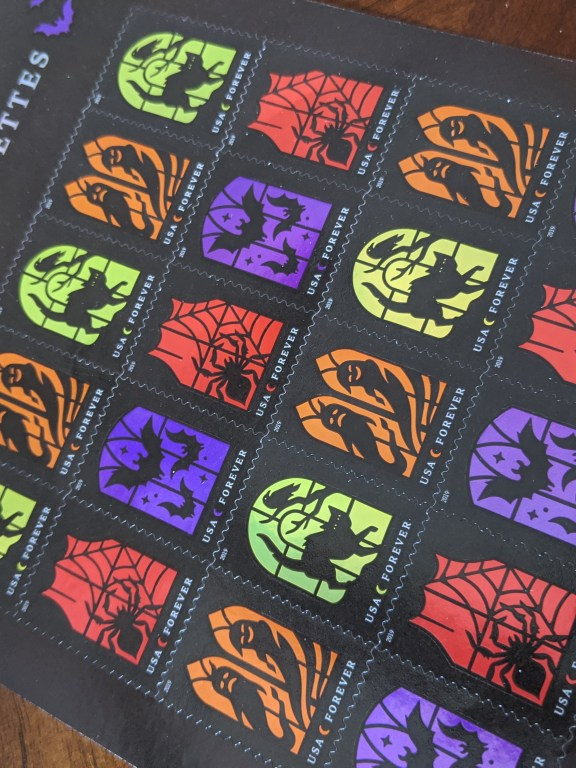 U.S. stamps themed Spooky Silhouettes. There are twenty stamps here. Four styles. Each looks like you're looking through a window. One has a yellow sky with a black cat and a raven in a tree. One has two ghosts in an orange sky. One has a spider in a web with a red background, and one has three bats with a purple sky and stars.