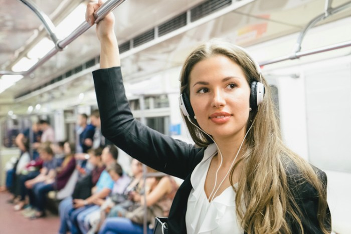 Beautiful Woman Listening Music On Her Smartphone On Subway Train