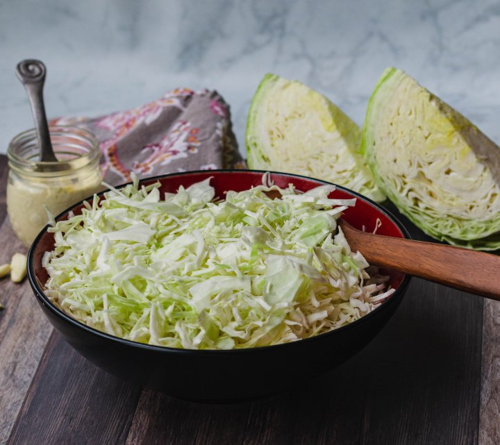 Bowl of coleslaw with a wooden spoon in it, in the background is a cloth napkin, garlic dressing for the coleslaw, and 2 wedges of cabbage