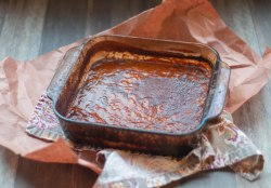 Pyrex filled with bbq sauce fresh from the smoker. The pyrex is laying on a piece of crumpled up parchment paper and a cloth napkin