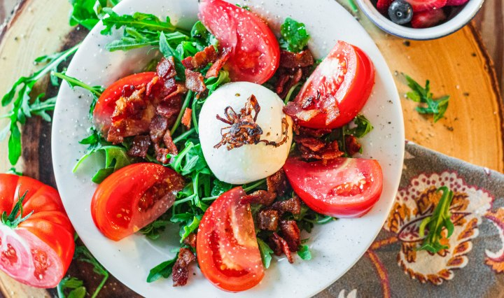 White bowl filled with arugula, wedged tomatoes, topped with burrata, bacon lardons, and crispy onions. The bowl is sitting on a round wooden lazy Susan with a live edge. There is a cloth napkin, tomato half and lettuce in the background.