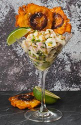 A martini glass filled with ceviche. There is a wedge of lime on the rim of the glass and 2 fried tostones in the back of the glass.