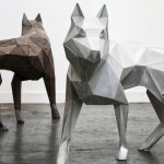 Two geometrically faceted wolf sculptures, rendered in steel and oxidized iron.