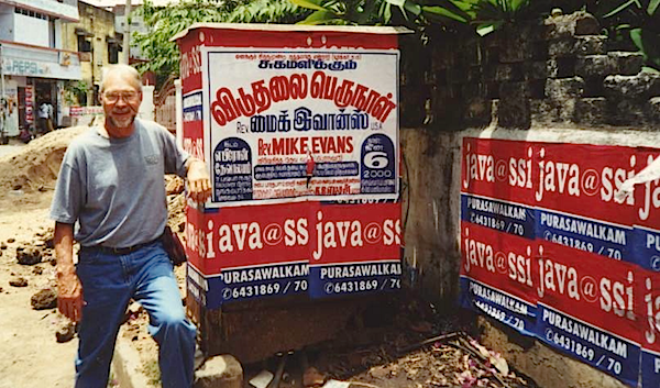 Mike Evans with poster announcing his conference in India