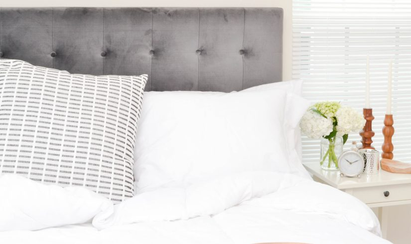 grey and white cozy bed with alarm clock