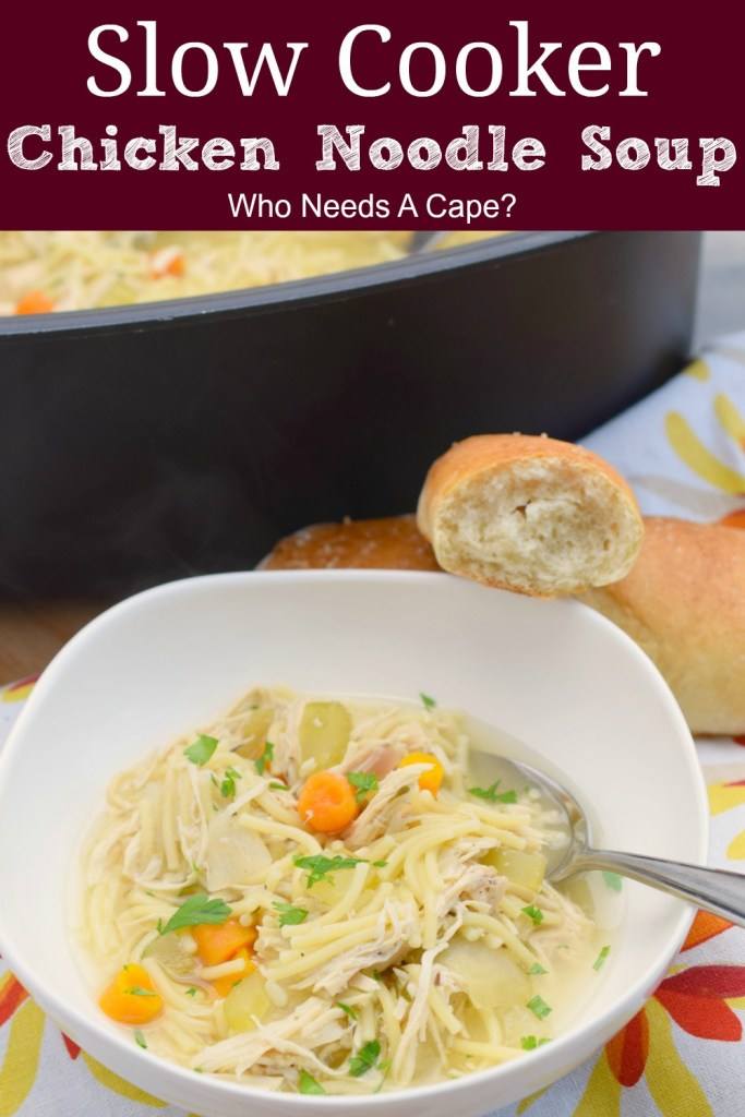 white bowl containing slow cooker chicken noodlel soup next to baguette and black slow cooker containing soup