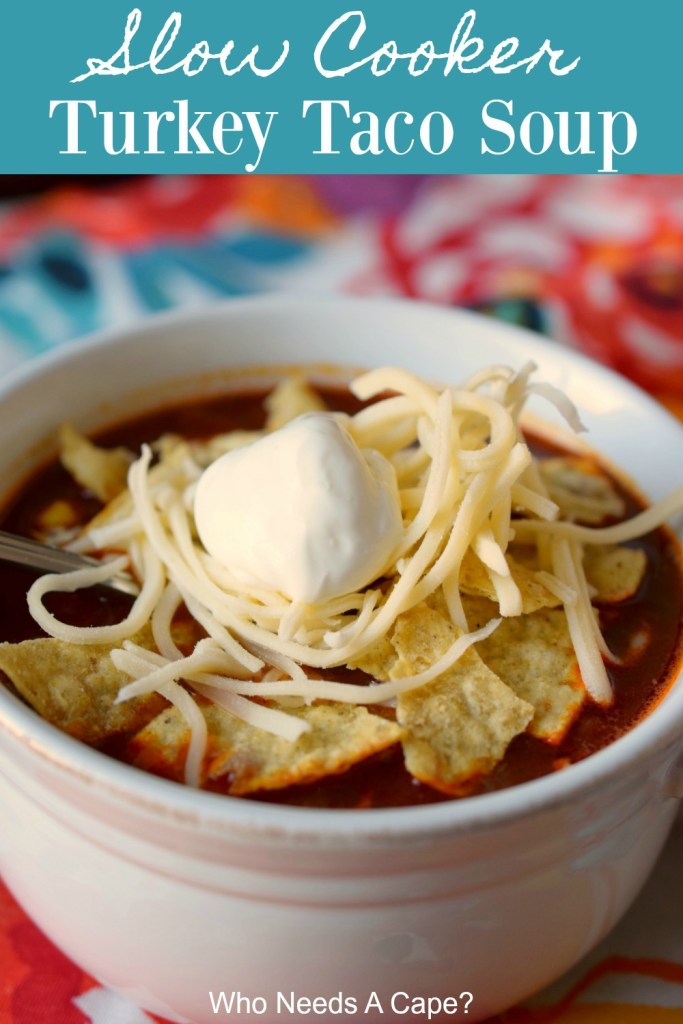 slow cooker turkey taco soup in white bowl topped with sour cream, shredded chees and tortilla chips on floral placemat
