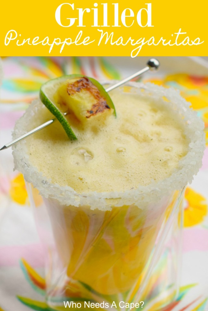 grilled pinepple margarita in glass with salted rim, garnish of lime and pineapple on silver spear sitting on glass, on top of brightly colored fabric
