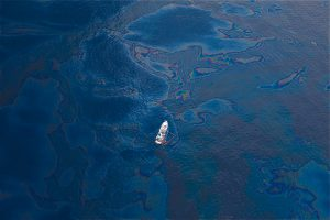 A ship floats in a sea of spilled oil in the Gulf of Mexico after the BP Deepwater Horizon oil spill. Photo by Kris Krüg.