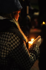 An attendee holds a candle during the vigil held at the University of Connecticut Storrs campus on Tuesday. (Photo by Santiago Pelaez)