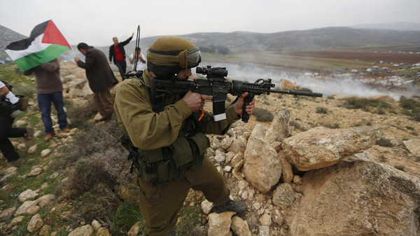 Israeli soldier aims his weapon during clashes with activists and Palestinian protesters following a demonstration against Israeli settlements in the West Bank village of Turmus Aya, near Ramallah