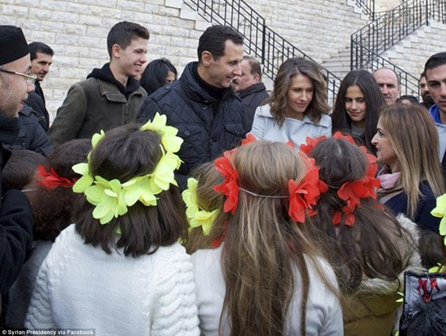 Syrian President Bashar Assad, centre left, and his wife Asma, centre right, speak with christian orphans during their visit to Sednaya Convent