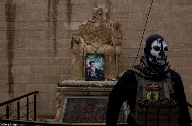 A soldier from the Iraqi Army Special forces stands guard in front of a defaced Christian statue during the Christmas mass