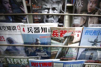 A magazine featuring U.S. President Donald Trump is on display with Chinese military magazines at a newsstand in Beijing, China, Tuesday, April 4, 2017. (AP Photo/Mark Schiefelbein)