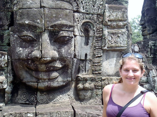 Smiling with a statue at Angkor Wat in Cambodia - A Year without Makeup