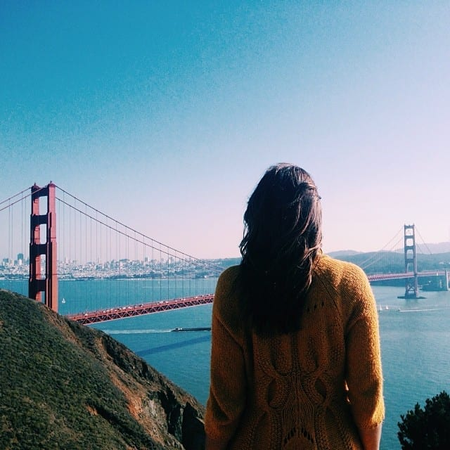 A Girl Standing in Front of the Golden Gate Bridge - How to Travel and Work Full Time