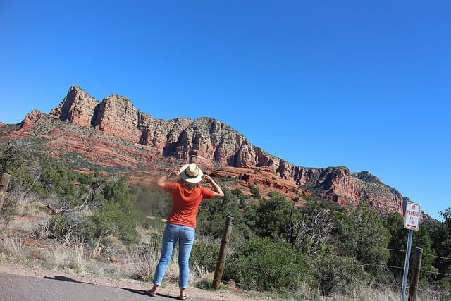 The Back of a Woman Looking Up at the Red Rocks - Pooping Your Pants on the Road