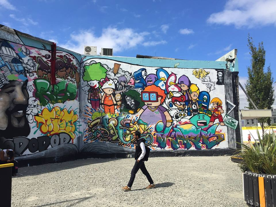 Graffiti on the walls of Christchurch, New Zealand as a pedestrian walks by