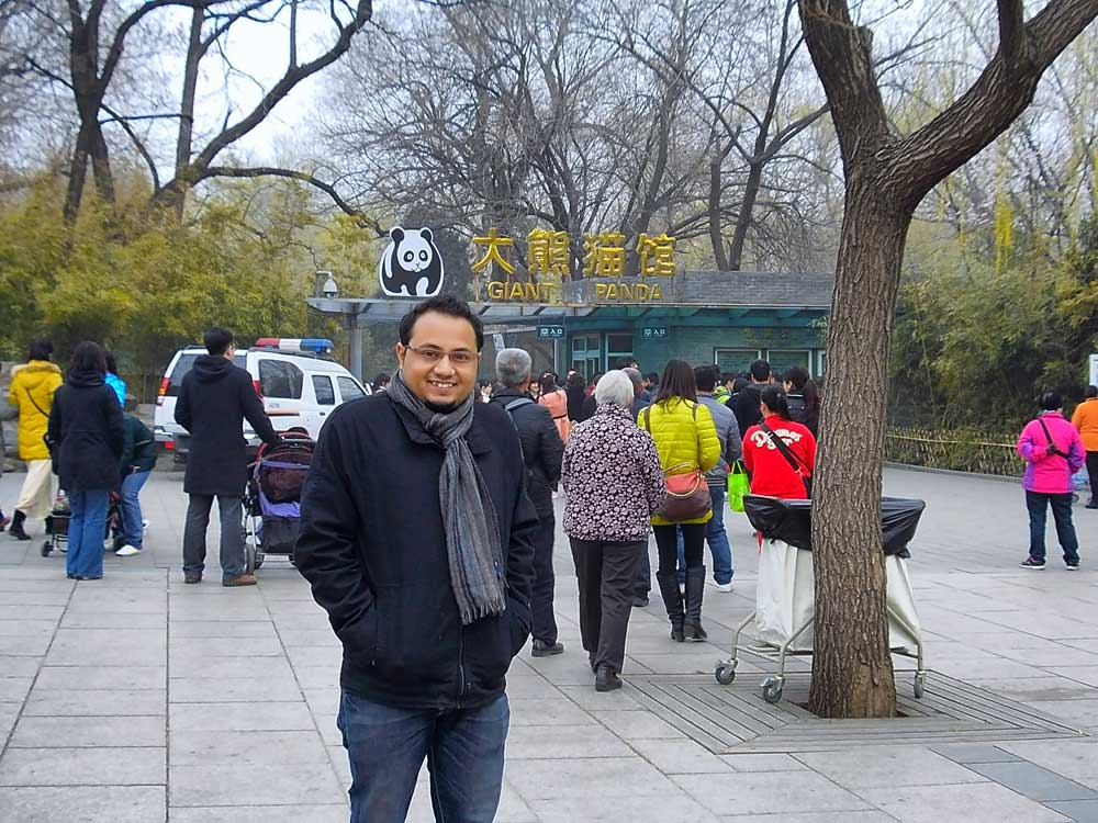 A man standing in front of the entrance to the Giant Pandas House at the Beijing Zoo